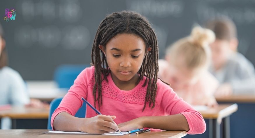 young girl writing at a desk in school