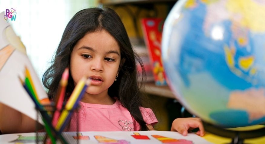 young girl studying with a globe of the world next to her
