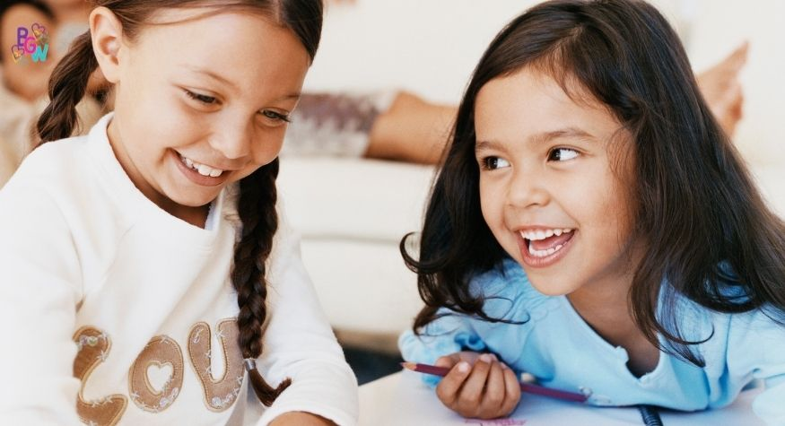 two young girls smiling and drawing